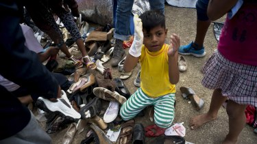 A migrant child holds a hand puppet while sitting on a pile of donated shoes at the Benito Juarez Sports Centre  in Tijuana, Mexico, on Saturday.