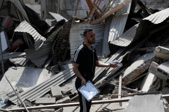 A man holds a child's shoe as he inspects buildings destroyed by Israeli air strikes in Gaza.