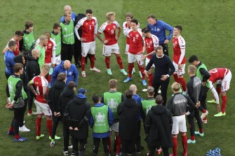 Denmark's manager Kasper Hjulmand speaks to his players after Christian Eriksen's cardiac arrest during the game against Finland.