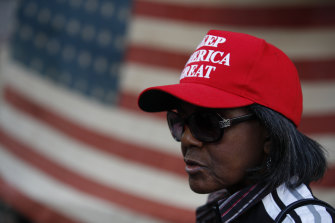 A woman stands in front of an American flag, as a handful of supporters of President Donald Trump protest outside the Pennsylvania Convention Centre, in Philadelphia, earlier this week.
