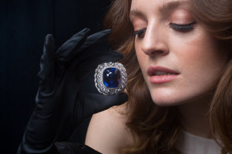 Caitlyn McMahon models the 118.88-carat sapphire that is on display in an exhibition by royal jeweller Garrard in Melbourne this week.