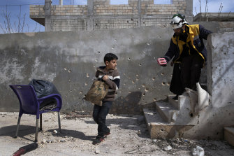 Muhammad Hussein Alloush, 10, collects items from his family home in Balyoun, Syria.
