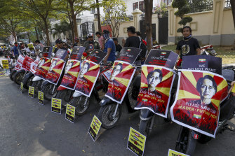 Soccer fans of Arsenal Football Club display placards against the military coup in their motorbikes in Mandalay, Myanmar.
