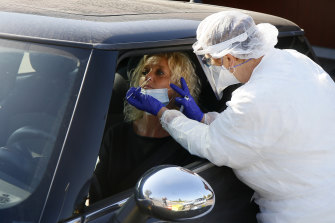 A medical worker takes a COVID-19 swab at a drive-through testing site in Wambrechies, northern France.