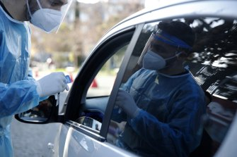 A medical worker conducts a COVID-19 rapid test on a woman at a drive-through testing site in Athens.