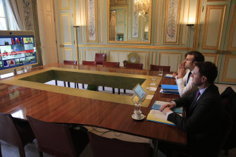 French President Emmanuel Macron and EU adviser Clement Beaune, front, during a video conference on the virus.