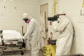Herald photographer James Brickwood is dressed in full PPE gear to document operations in a Sydney morgue.