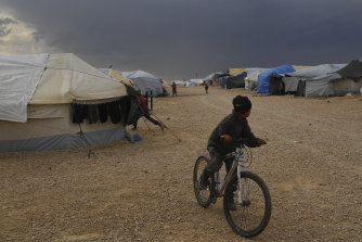 A boy on a bike looks back toward the dark clouds approaching the camp.