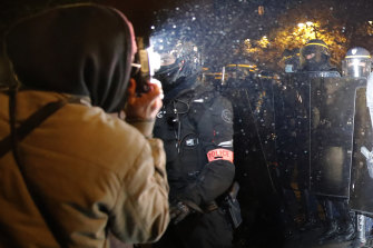A demonstrator takes a picture of police officers during a protest against the bill restricting images of police.