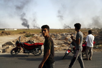 People at the Turkish-Syrian border watch smoke billowing from targets inside Syria during bombardment by Turkish forces.
