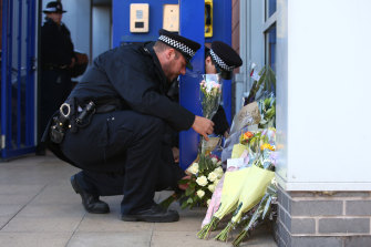 Metropolitan Police collect floral tributes at Croydon Custody Centre following the shooting.