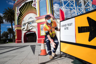 A sign outside Luna Park points to a pop-up testing site in the Palais car park in St Kilda.