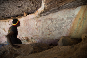 Traditional owner Ian Waina inspects a painting of a kangaroo that is more than 12,700 years old.