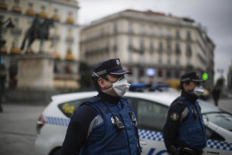 Police officers wearing face masks hold a minute of silence for the victims of COVID-19 as the lockdown to combat the spread of coronavirus continues at the Sol square in Madrid, Spain.