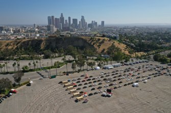 Cars line up at a COVID-19 drive-through testing site in the parking lot of Dodger Stadium last week.