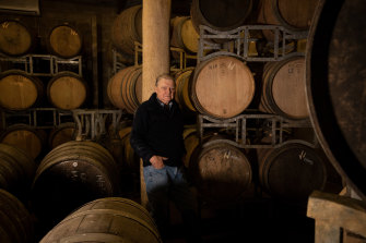Ken Eckersley stands among empty barrels that would normally full of red wine from 2020.