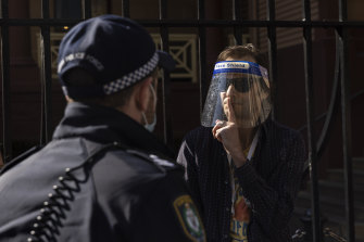 A protestor gestures towards a police officer outside NSW Parliament House on Tuesday.