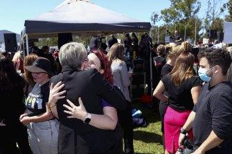 Tanya Plibersek hugs Saxon Mullins at the March 4 Justice protest.