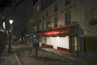 A man pushes his bicycle along a row of closed restaurants in Montmartre, Paris, during a late curfew.