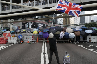 Grandma Wong waves the Union Jack as other protesters use umbrellas to shield themselves outside the Legislative Council in Hong Kong, in June 2019. She says she was detained in August then prevented from returning to Hong Kong.