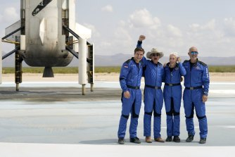 Oliver Daemen, from left, Jeff Bezos, Wally Funk and Bezos' brother Mark in front of the New Shepard rocket in Texas.