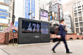 A commuter walks past the reset countdown display of the Tokyo Olympic Games outside the JR Shinbashi Station in Tokyo, Japan.