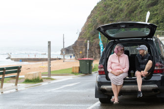 Women sheltering from the rain at Bilgola Beach this morning .