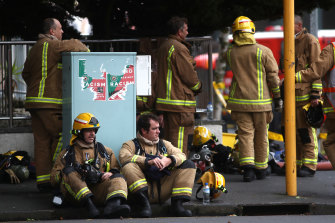 Firefighters take a break outside on Wednesday.
