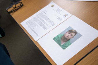 An image of the accused, Robert Aaron Long, is displayed near a press release provided by the Cherokee County Sheriff's Office on Wednesday.