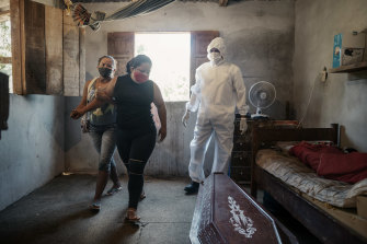 Elen Ferreira do Nascimento is comforted as workers take the body of her mother, who died at home during the coronavirus pandemic, in Manaus.