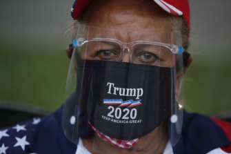 A supporter of President Donald Trump wears a mask and face shield as supporters gather for a car caravan of hundreds of vehicles, at Tropical Park in Miami.