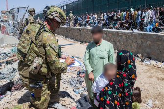 Major Tim Glover, part of the 1st Battalion, Royal Australian Regiment, assists the Department of Foreign Affairs and Trade with locating Afghan Australian visa holders at the congested Abbey Gate at Hamid Karzai International Airport, later the scene of a deadly Islamic State attack.