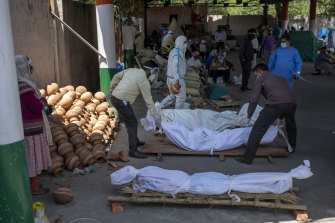 People line up dead bodies of those who died of COVID-19 at a crematorium, in New Delhi.