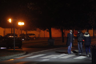 French police officers gather at the scene of the teacher's death in Conflans Sainte-Honorine.