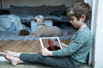 Fin Bowden, 7, is taught maths by his grandfather John Evans, who lives in Canberra.