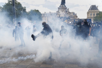 A man kicks a tear gas canister during a march against police brutality and racism in Paris on Saturday, June 13.