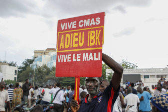 A man holds a sign saying goodbye to IBK, referring to Malian President Ibrahim Boubacar Keita, as soldiers parade in the capital on Tuesday.