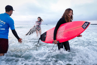 Let's Go Surfing in Byron Bay is barely surviving with the help of JobKeeper, but some people are still braving the cold including instructor Blake Whittaker with surfers Jade Stewart and Ebony Conrick.