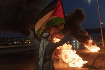 A protester flies a Palestinian flag during clashes with Israeli troops in Nablus this month.