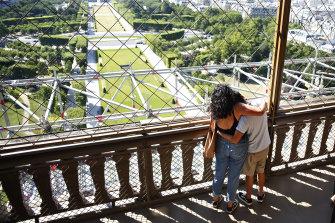 Two people hug on the Eiffel Tower in Paris.