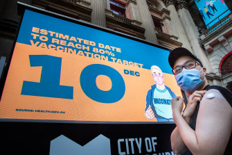Recently vaccinated Edbert Limen poses in front of the big screen at Melbourne Town Hall displaying Victoria's vaccination tally on Thursday.