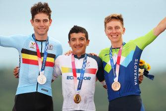 Silver medalist Wout van Aert of Belgium, left, gold medalist Richard Carapaz of Ecuador, centre, and bronze medalist Tadej Pogacar of Slovenia, pose on the podium.