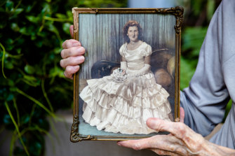 Pamela Mountfort holding a photo of her younger sister, Pat McDonald, at a Sydney university ball in a dress made by her mother.