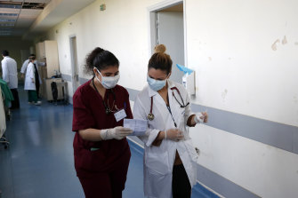 Medical student Adamantia Papamichail, left, shares notes with staff doctor Katerina Bakiri.