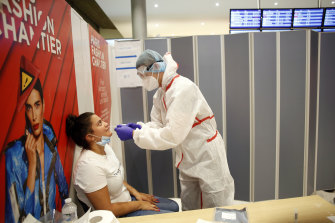 A health worker collects a nasal swab at Roissy Charles de Gaulle airport, outside Paris.