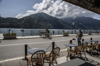 A cyclist rides past cafe tables in Tremezzo, Lake Como, Italy.