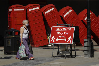 """A social distancing sign is displayed in front of """"Out of Order"""" a 1989 red phone box sculpture by British artist David Mach, in London."""