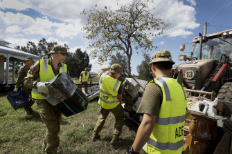 Defence personnel help clear flood-damaged furniture and belongings at Em Trotter's home in Croki near Taree.