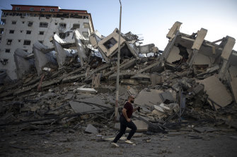 A Palestinian man passes by the remains of a building destroyed by Israeli airstrikes on Gaza City.
