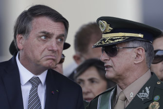 Brazilian President Jair Bolsonaro, left, talks with Army Commander General Edson Leal Pujol, during a military ceremony. Pujol has resigned along with the chiefs of the navy and the air force. The Armed Forces have repeatedly said they would not be drawn into politics.